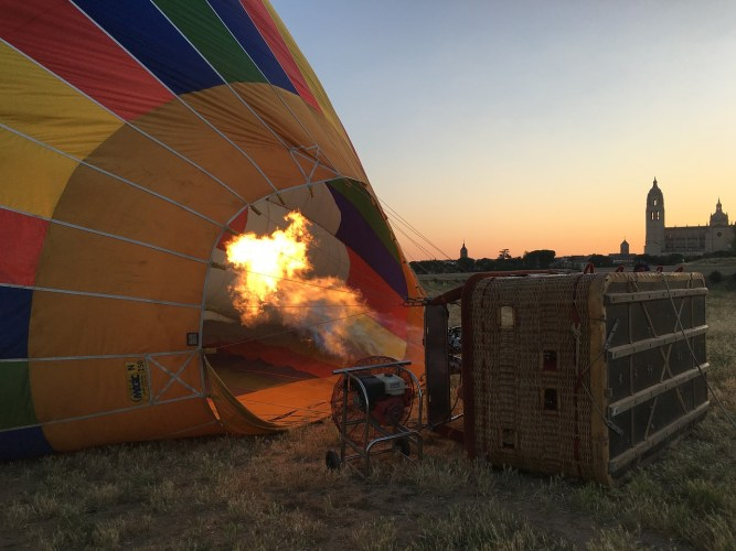 Hot air balloon being filled with fire and a fan.