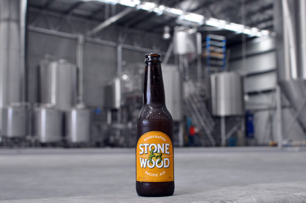 A bottle of Pacific Ale in front of the large new brewery