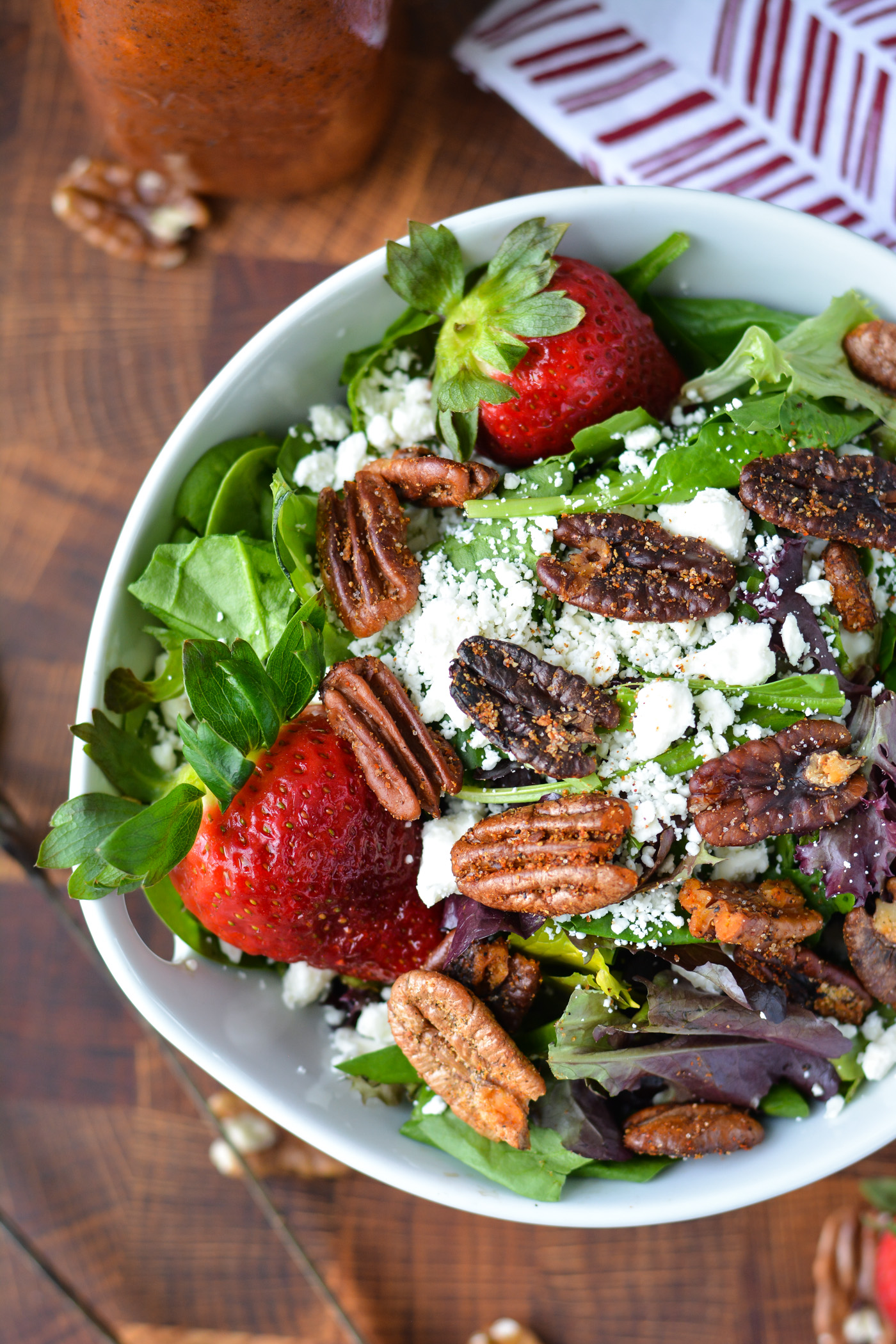 overhead shot of a salad made of mixed greens, feta cheese, fresh strawberries, and spiced pecans