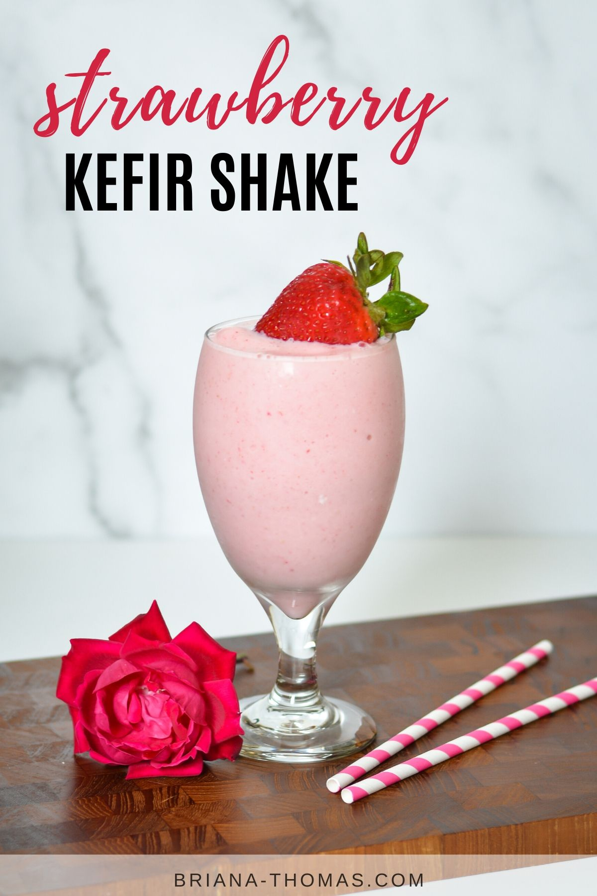 strawberry kefir shake in glass goblet topped with a fresh strawberry