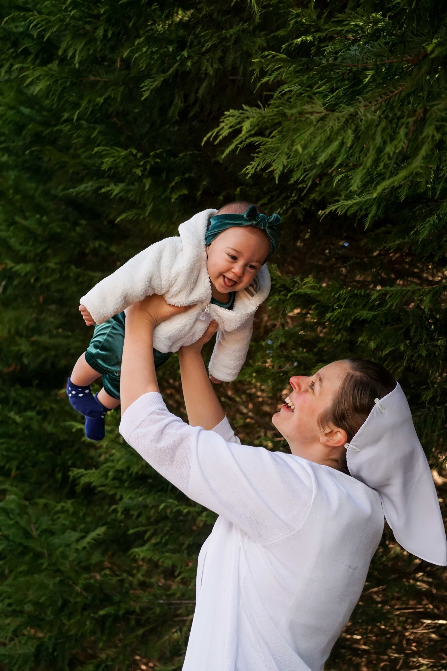 The pictures in this post are taken in front of some Leland Cyprus evergreen trees, which make for a rich, deep green background. Briana is wearing a white dress with a white open-down-the-front sweater and has a white prayer veiling on her head. Hadassah is wearing a green velour romper with matching headband, a fluffy white jacket, and navy socks with white polka dots. In this picture, Briana is holding Hadassah up in the air over her head. Both are smiling!