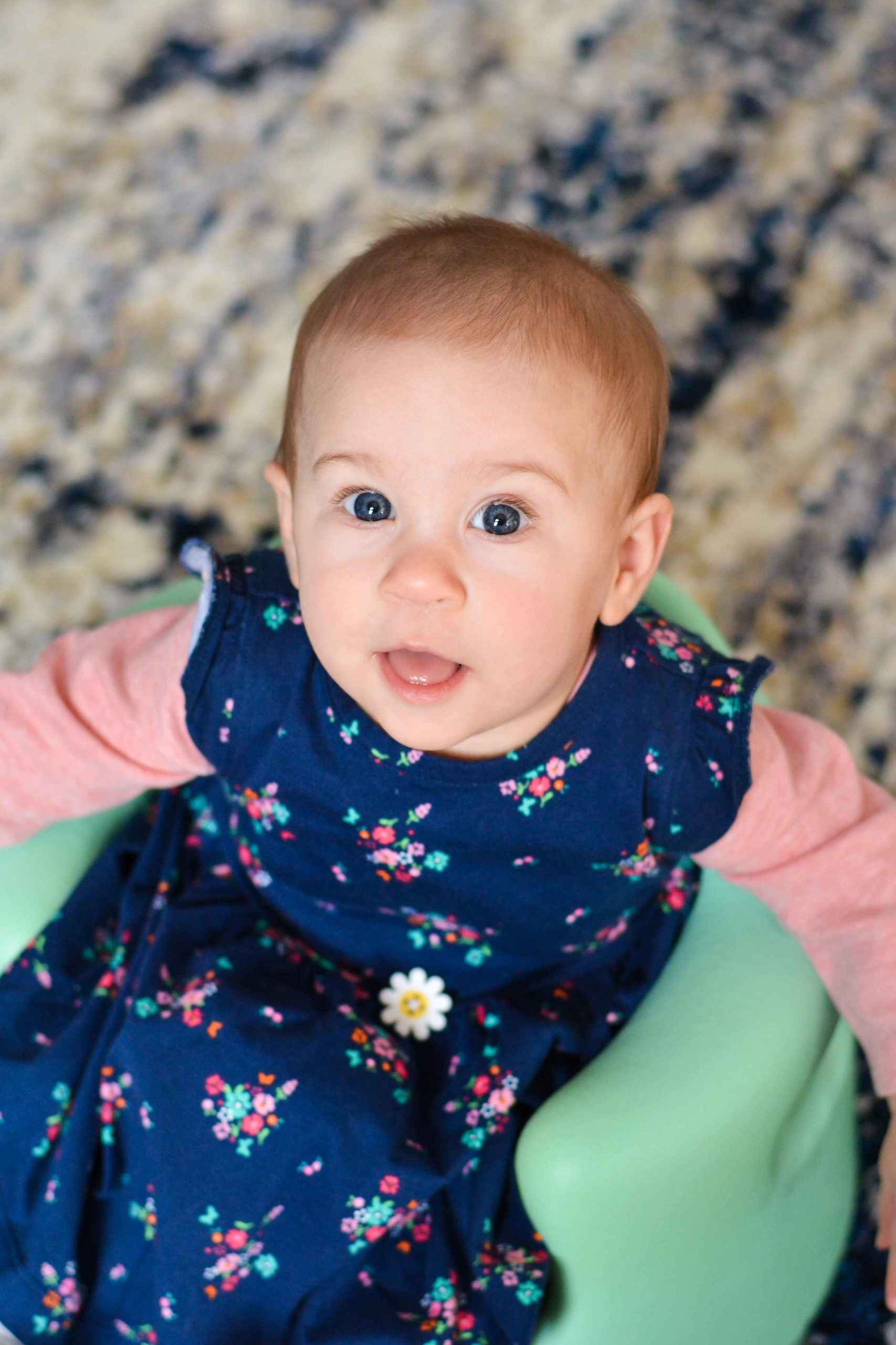 Hadassah is wearing a long sleeved salmon colored onesie covered by a navy blue floral jumper with a daisy-shaped button sewn at the center of the waist seam. She's sitting up in a mint green molded rubber Bumbo seat and is looking up at the camera with big blue eyes and a partial smile.