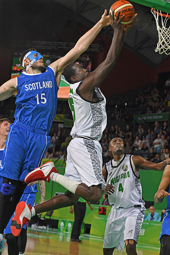 Nigeria's Musa Usman goes up to shoot as Scotland's Alasdair Fraser tries to block during the Men's Qualifying Finals basketball game between Scotland and Nigeria at the XXI Commonwealth Games in Cairns - image by Brian Cassey