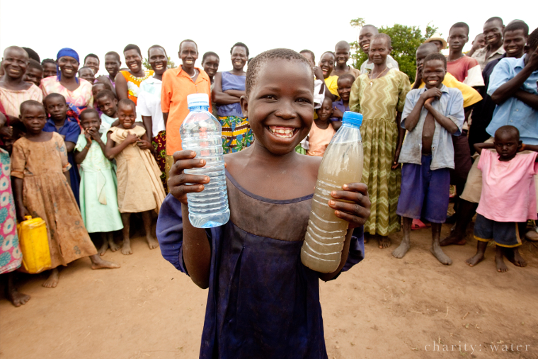 Ugandan holding two bottles: one with dirty water, the other with clean water
