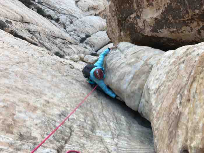 Sadie near the top of P2 of solar slab getting through a little off width section of the inner crack