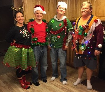 a family of four stands prominently displaying their ugly christmas sweaters