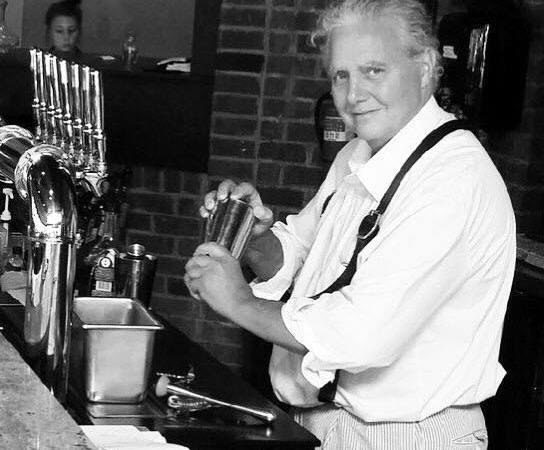 Chef Needham mixes vintage cocktails behind the bar.