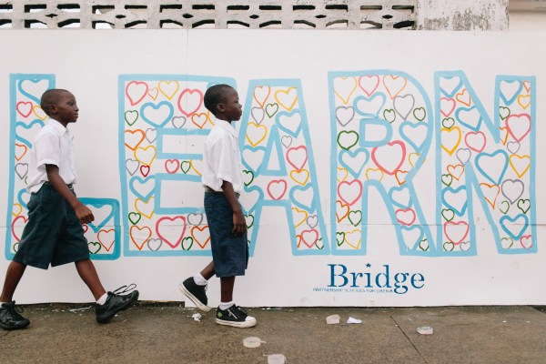 "Bridge PSL pupils walk in front of the word ""learn""."