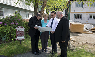 RESIDENCE FOR RETIRED PRIESTS—Bishop Caggiano, Vickey Hickey, administrator of Queen of Clergy, Andrew Schulz, director of real estate for the diocese, and Msgr. William Scheyd, episcopal vicar for retired priests, look over drawings for the Queen of Clergy expansion on Strawberry Hill Avenue<span id=