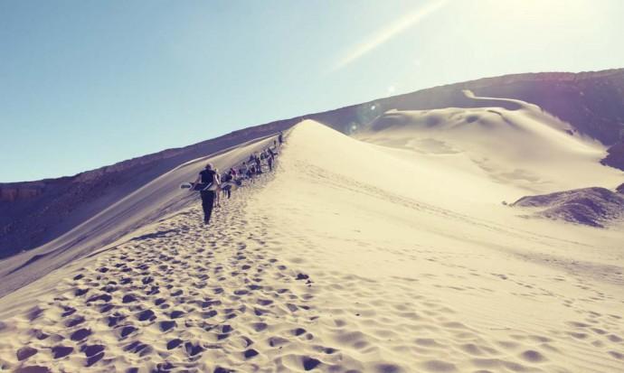 Climbing the dune while sandboarding in San Pedro de Atacama