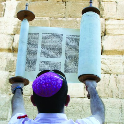 A Man Holding A Torah Scroll at the Western Wall