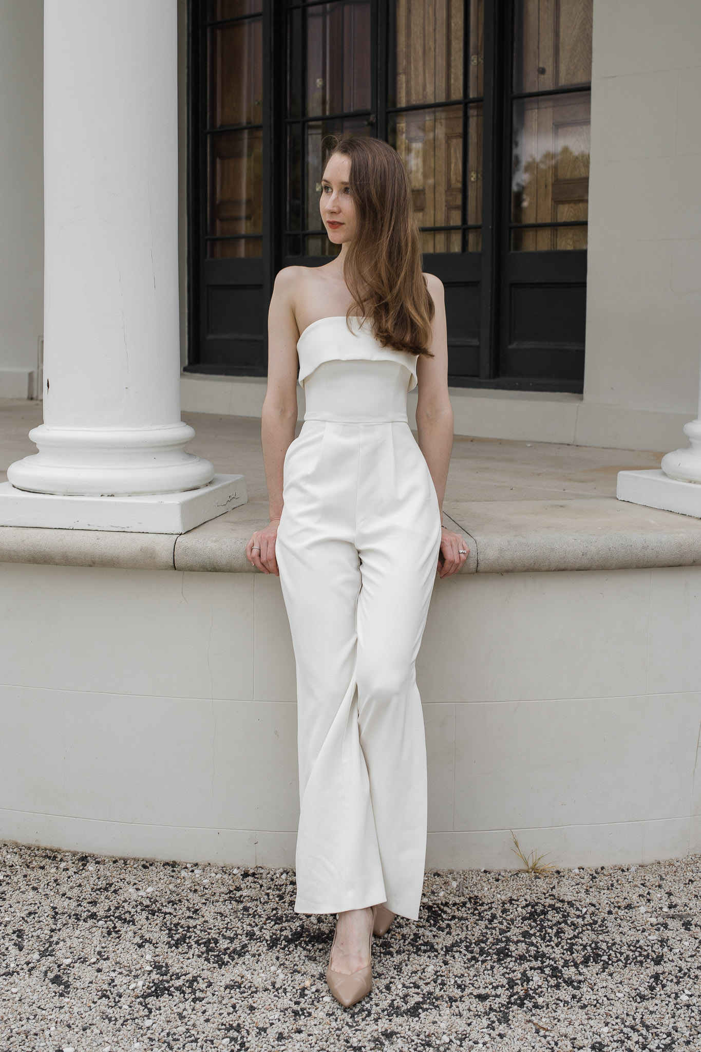 Girl wearing a white jumpsuit standing in front of the columns of Tempe House, Sydney. Engagement outfit inspiration, bridal shower outfit ideas, minimalist wedding ideas
