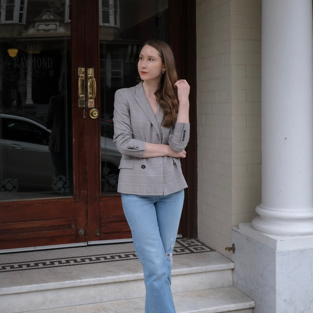 Girl wearing a grey plaid blazer, black body suit and blue Levi's Ribcage Straight Ankle Jeans standing on the steps of a buidling There is a column to her left. Simple outfit ideas, easy fashion, casual fashion looks, denim outfit ideas, less is more, quality over quantity, sustainable fashion, slow fashion blogger, minimalist fashion blogger