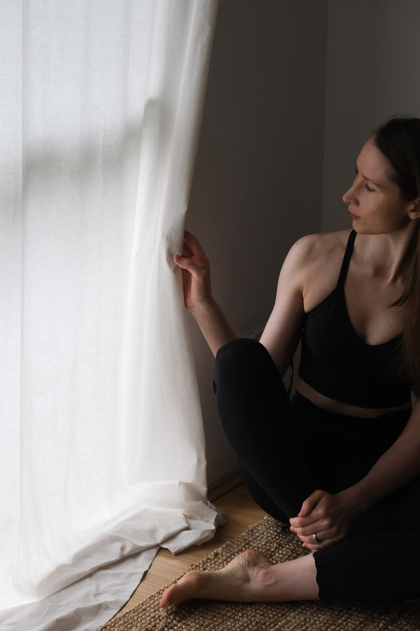 Girl standing in front of white curtains wearing DK Active Chloe crop and Dharma Bums 7/8 Scollop leggins in black, sustainable active wear review, DK Active wear review, sustainable clothing, minimalist active wear, active wear capsule wardrobe