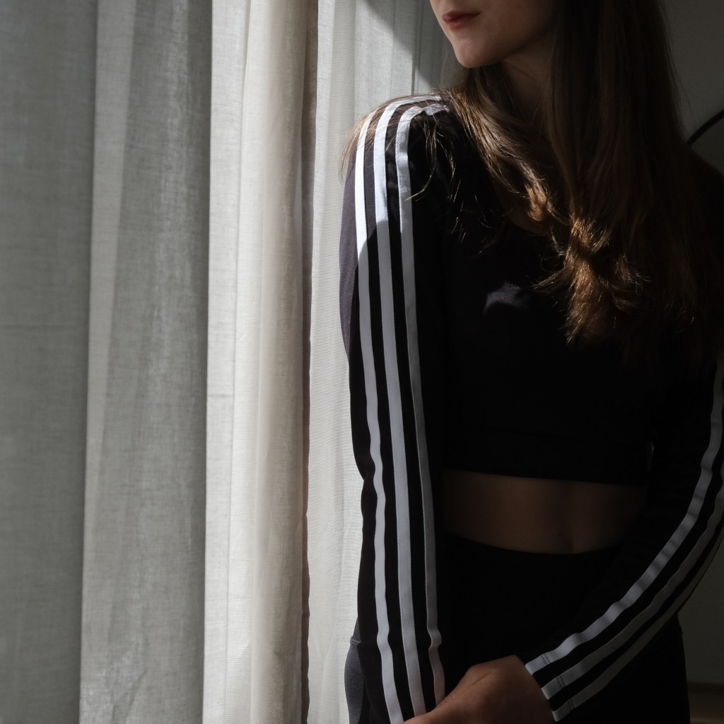 Girl sitting in front of white curtains wearing Adidas crop and Dharma Bums 7/8 Scollop leggings in black, sustainable active wear review, Adidas sustainability review, sustainable clothing, minimalist active wear, active wear capsule wardrobe