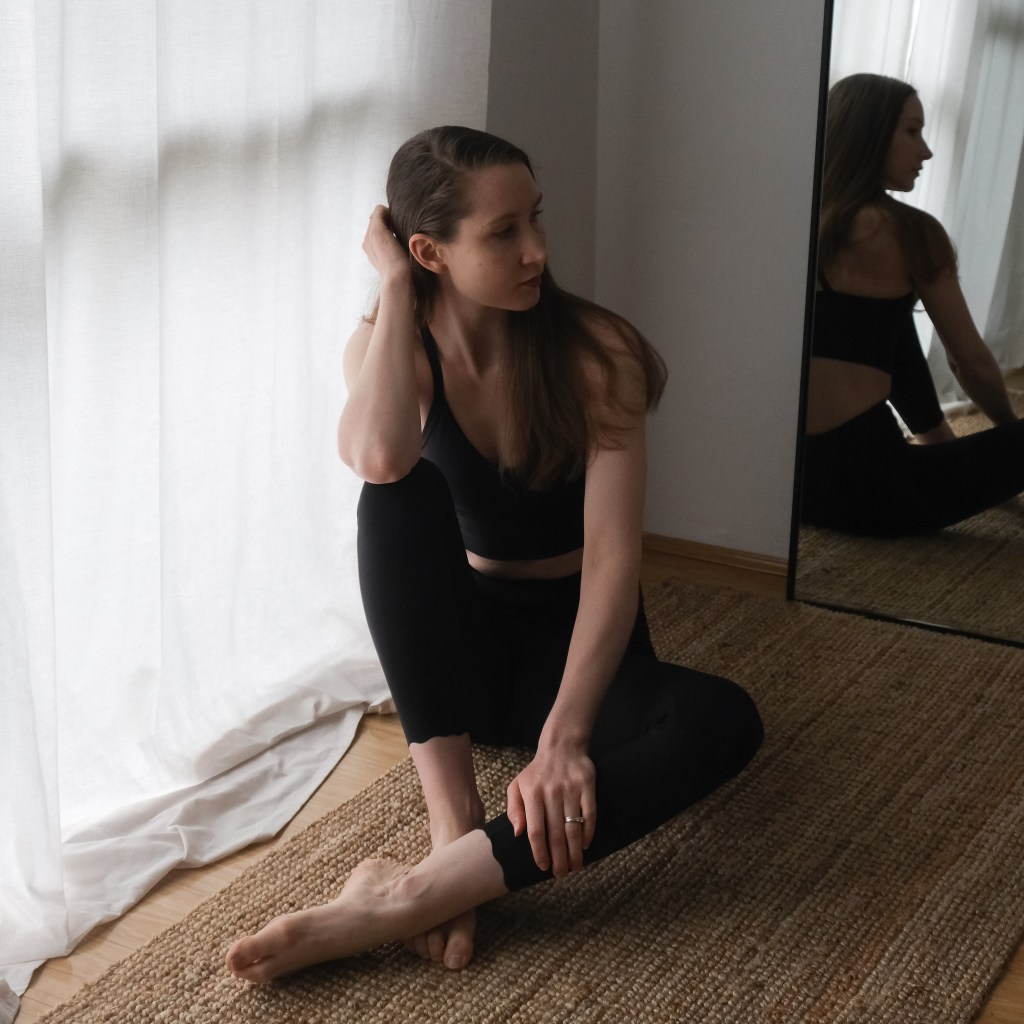 Girl sitting in front of white curtains wearing DK Active Chloe crop and Dharma Bums 7/8 Scollop leggins in black, sustainable active wear review, DK Active wear review, sustainable clothing, minimalist active wear, active wear capsule wardrobe