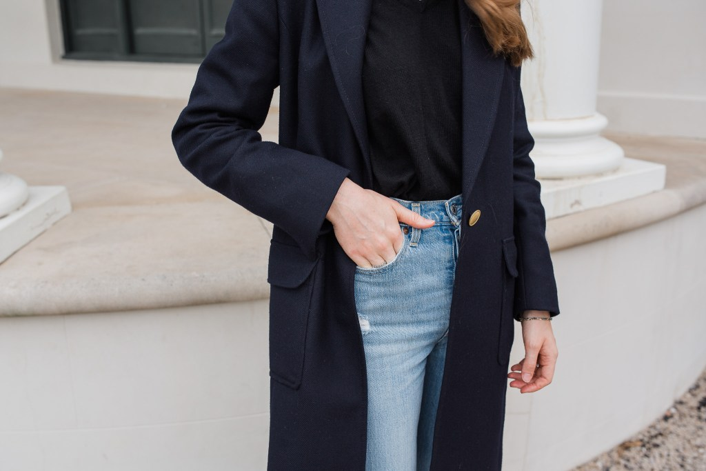 Girl standing in front of old building in Sydney wearing a navy blue sportscraft coat, a black woollen knit and levi's ribcage straight ankle jeans. Winter essentials, winter layering tips, winter outfit ideas