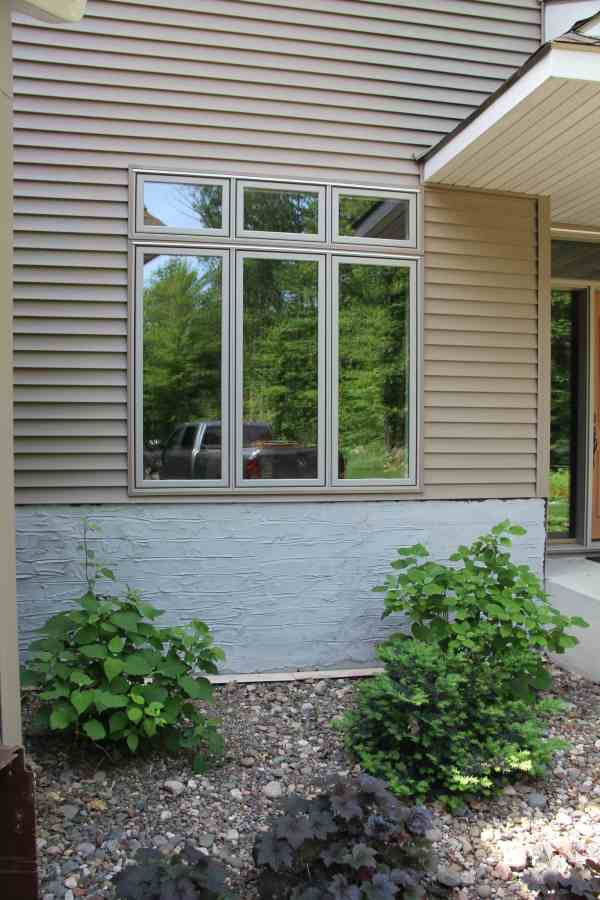 Scratch coat cement layer for adding rock to home exterior