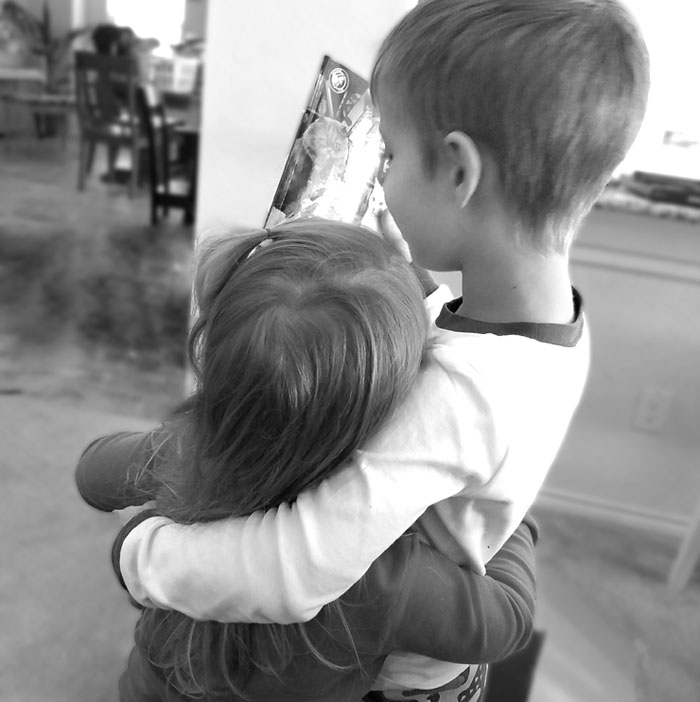 Two young children hugging