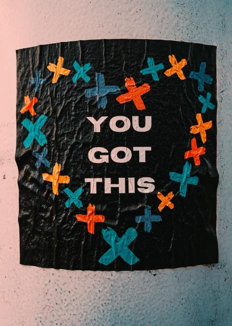poster reading 'you got this' surrounded a heart-shaped outline composed of multicolored crosses