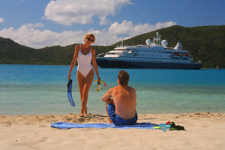 A woman coming out of the sea after snorkeling, walking toward a man on the beach, in front of a cruise ship