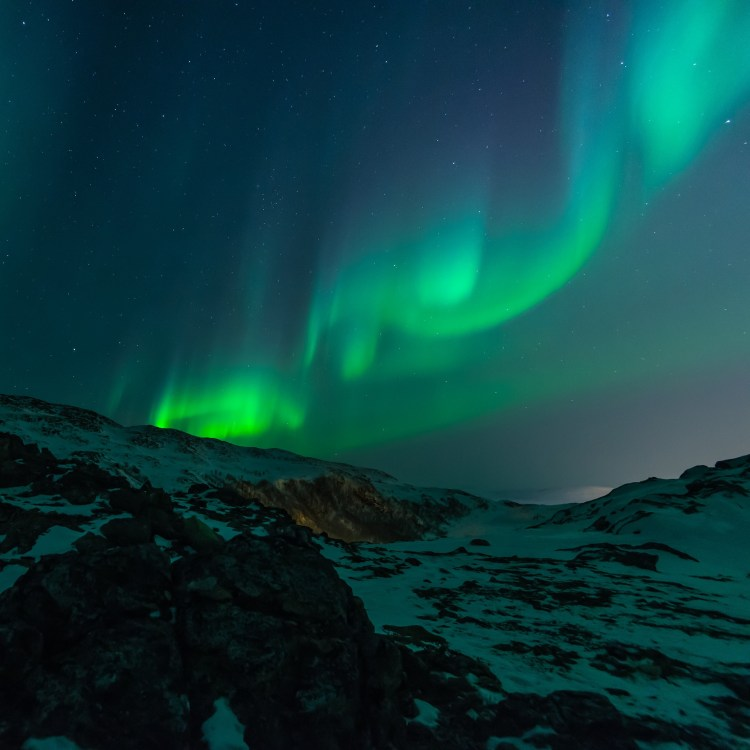 The Northern Lights against a mountaintop