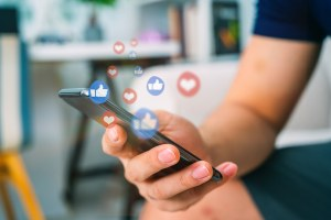 Celular com holograma de reações nas redes sociais.