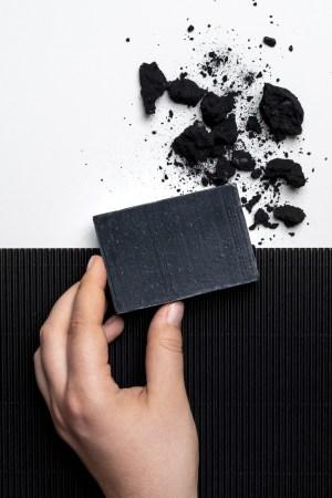 Eine Hand hält eine schwarze Gesichts- und Körperseife mit Aktivkohle