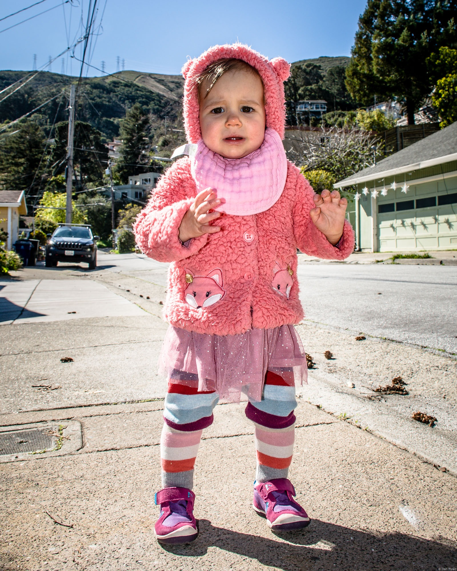 an unhappy toddler in pink