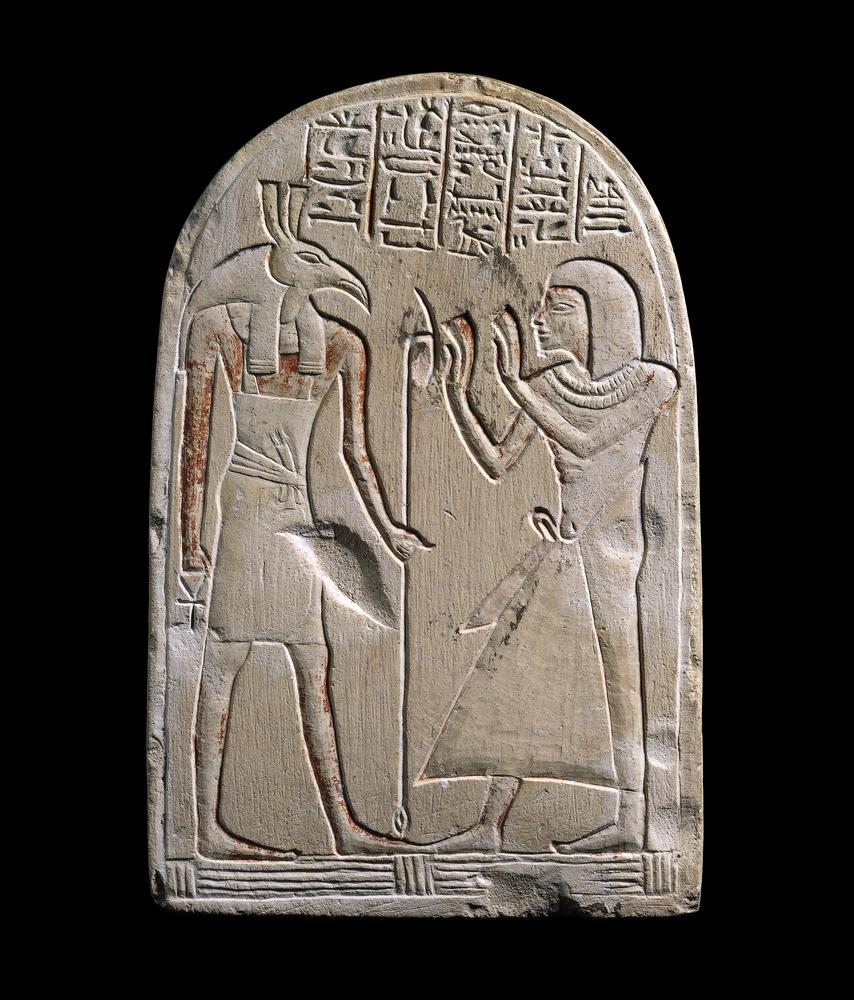Sandstone Egyptian tablet showing Seth and a worshipper with traces of paint and hieroglyphs