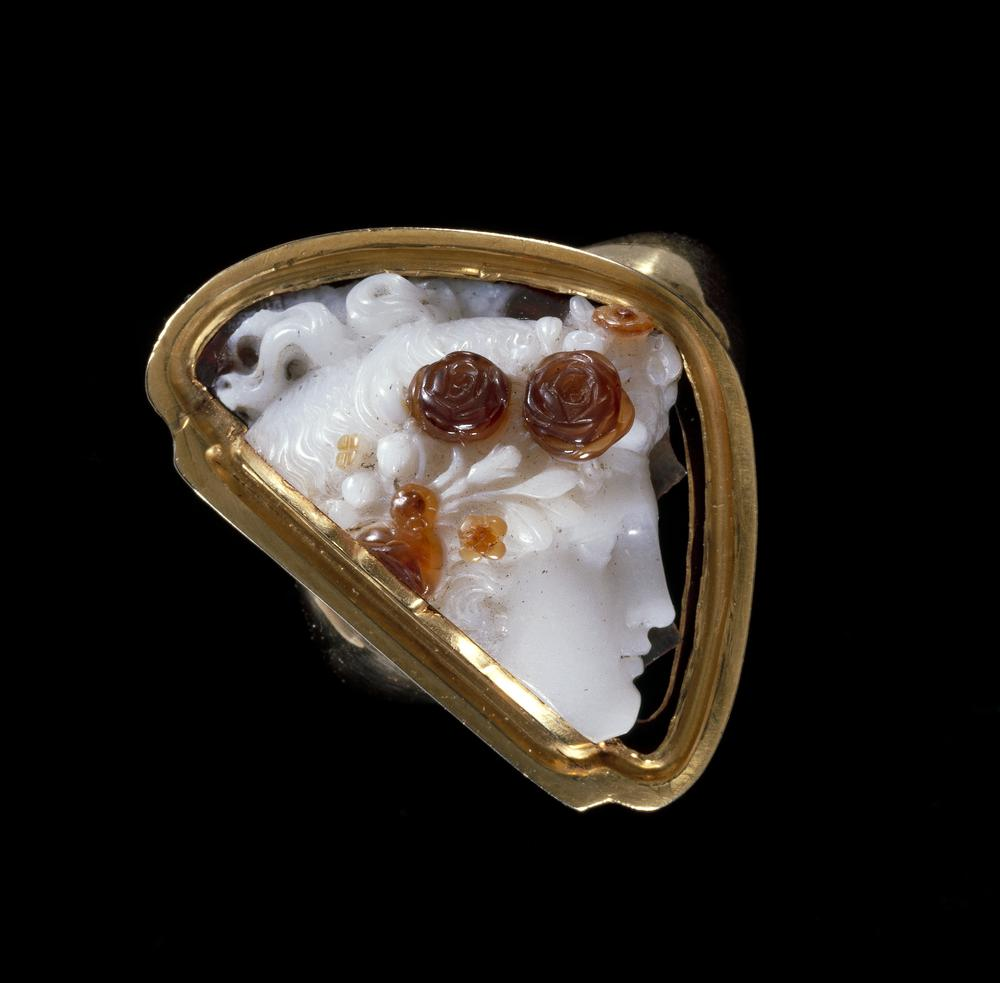 Cameo; carnelian breccia; the 'Flora of Pistrucci'; part of head of Flora to right in high relief, wearing wreath of roses, poppies and marguerites(?); stone ground at back; what remains of lowest stratum is cut very thin; roses in a red stratum.
