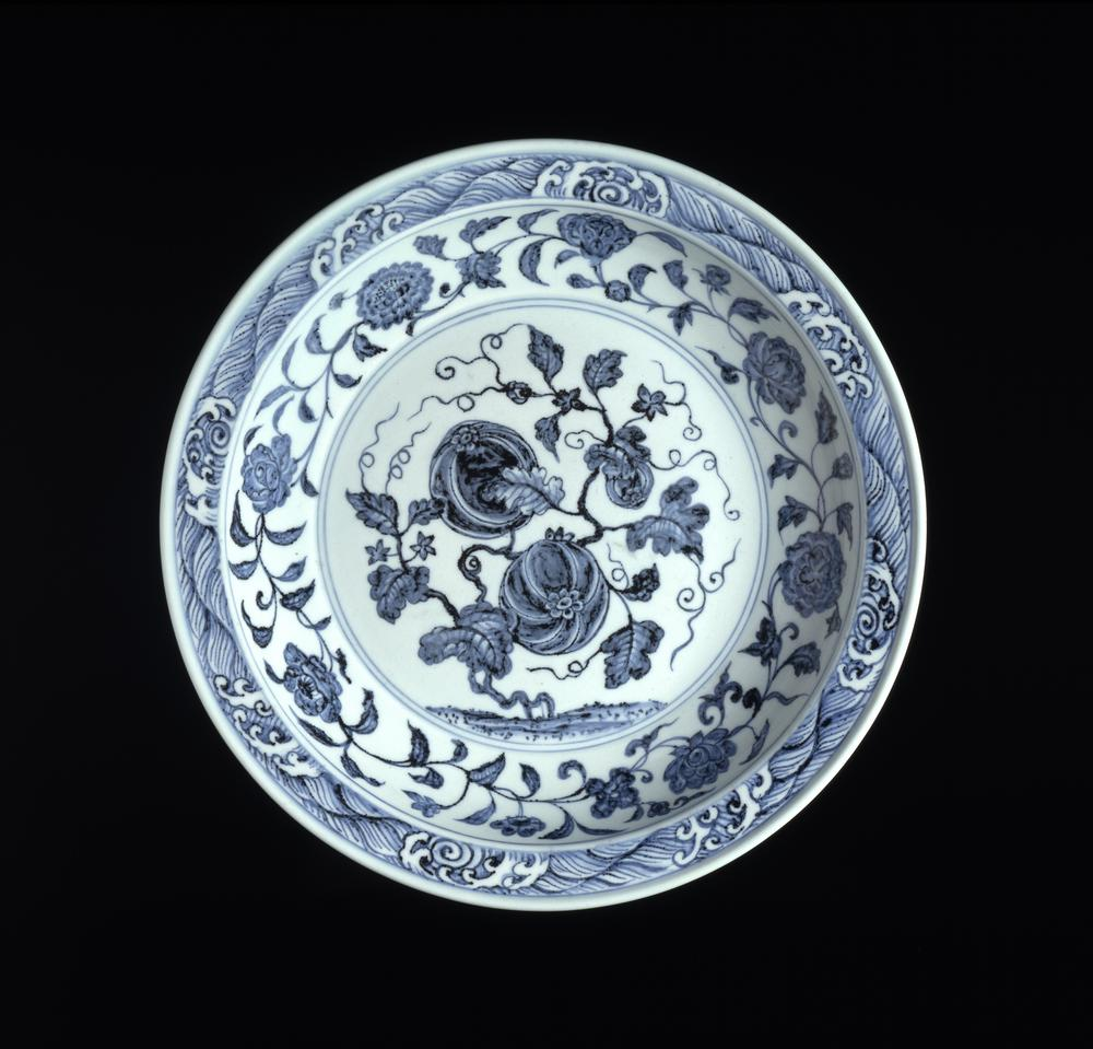 Large porcelain dish decorated in underglaze blue with a fruiting and flowering melon plant; the well with eight flowering plants in a continuous scroll, including pomegranate, tree peony, herbaceous, peony, lotus, rose, camellia, rose and chrysanthemum; the rim with a wave border with crests reserved in white; the outside with six separate sprays of auspicious fruiting plats: cherry, ginkgo, peach, lychee, grape and pomegranate; the base unglazed.