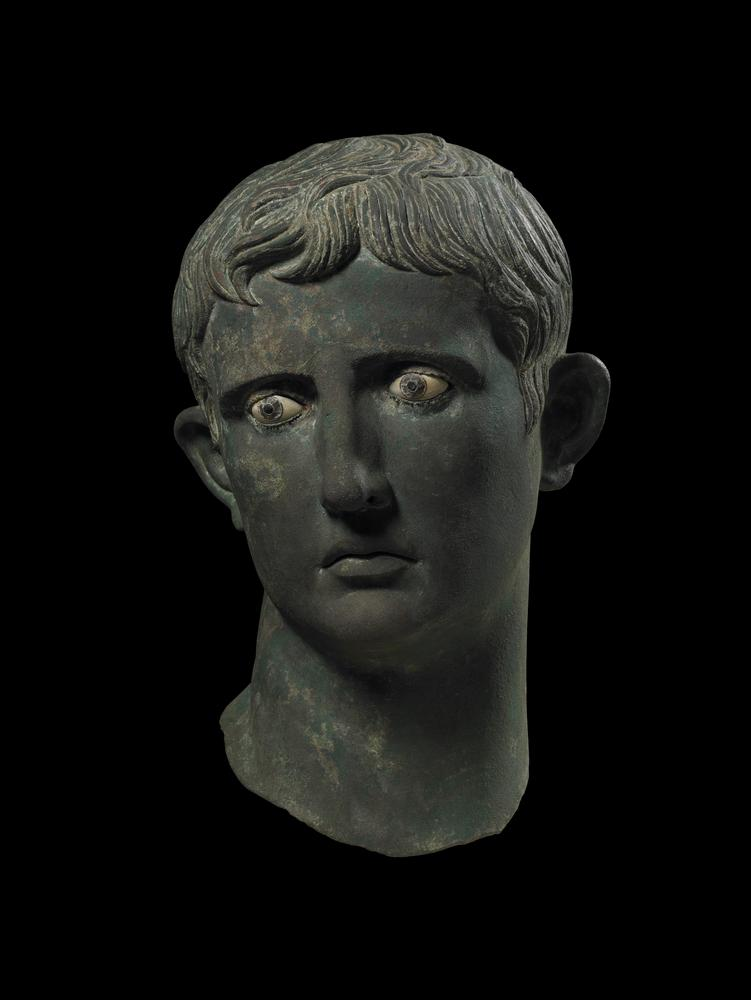 Bronze head from an over-life-sized statue of Augustus: the head is broken through the neck but is otherwise in an excellent state of preservation.  There are four fragments of plaster from the head. The eyes are inlaid, with glass pupils set in metal rings, the irises of calcite. The eyebrows are plastically rendered. The emperor's head is turned to his right, with the pronounced twist to the neck typical of Hellenistic work. The hair falls on the brow in the divided and curving cut that marked most of Augustus's portraits as emperor.  The facial planes are broad. The mouth is slightly downturned, a feature of late Hellenistic portraiture. The ears project markedly, the upper lobes bending forwards.