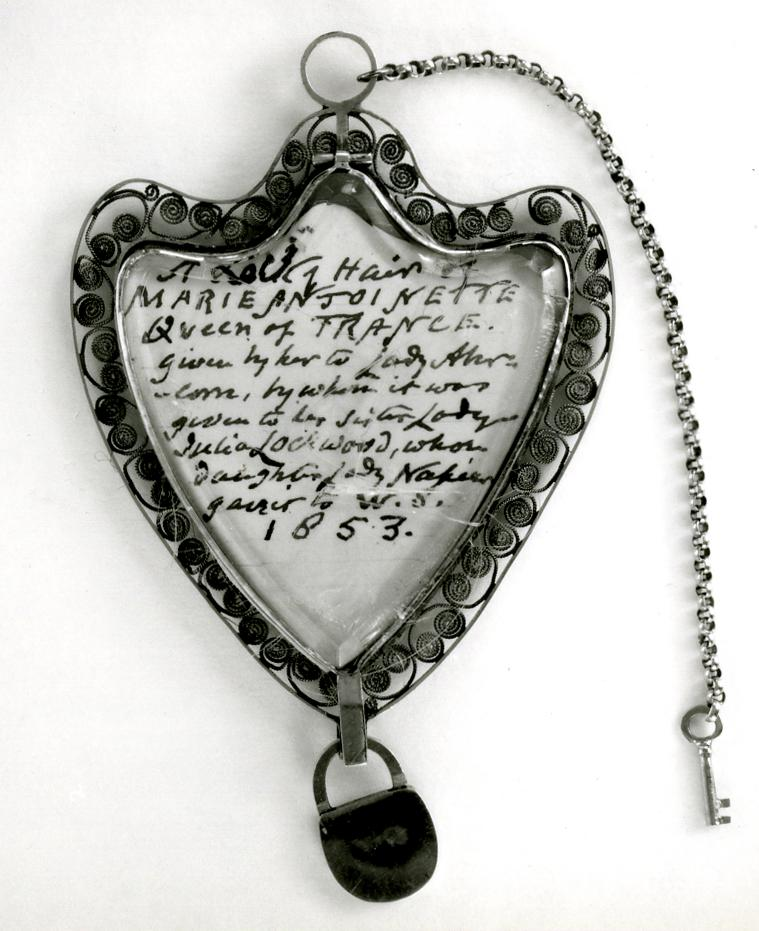 Heart shaped pendant locket with the hair of Marie Antoinette set under glass or rock-crystal with an inscribed card and mounted in a gold filigree frame. A small gold padlock is suspended from the base with a key on a chain attached to the suspension loop.