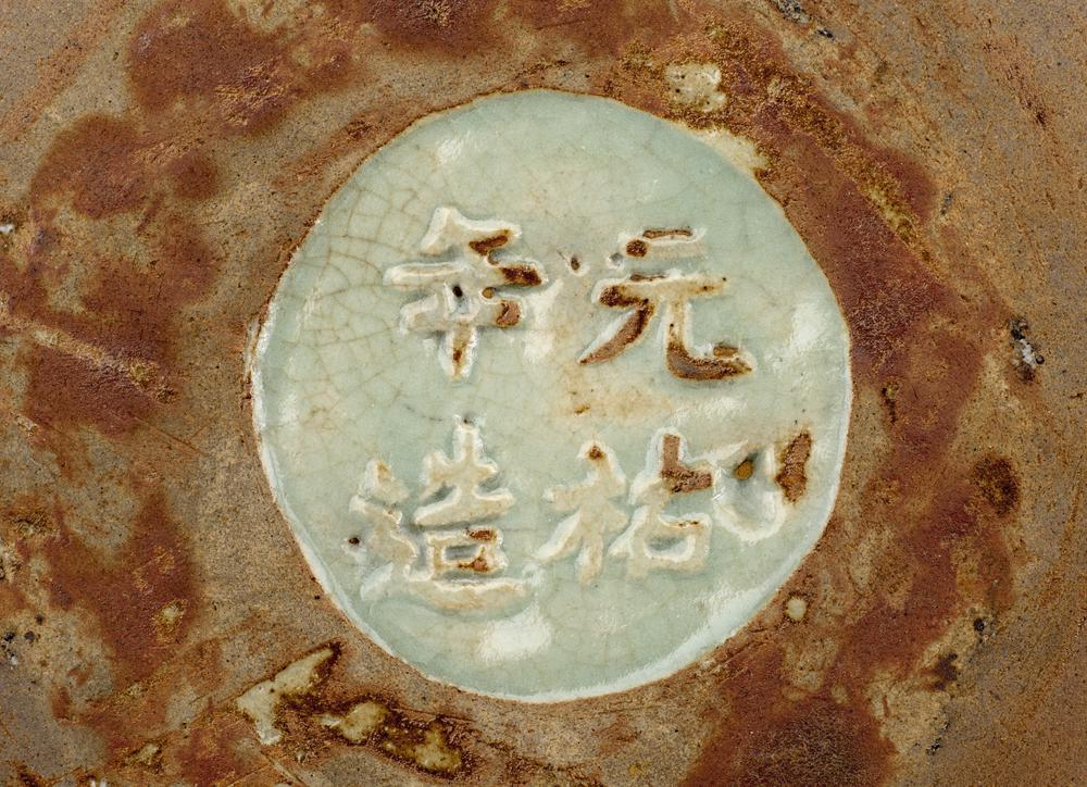 Longquan porcelain dish.  The dish has crackled greyish green glaze. There is a peony spray in low relief in the centre, with overlapping lotus petals on the interior. There is an inscription on the base.
