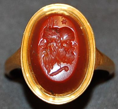Red jasper gem engraved with the conjoined masks of Pan and Seilenos; above is a star, below is a shepherd's crook.