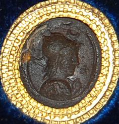 Gem of glass paste imitating sard, engraved with a bust of Athena wearing a helmet and aegis; in the field is a star and crescent.