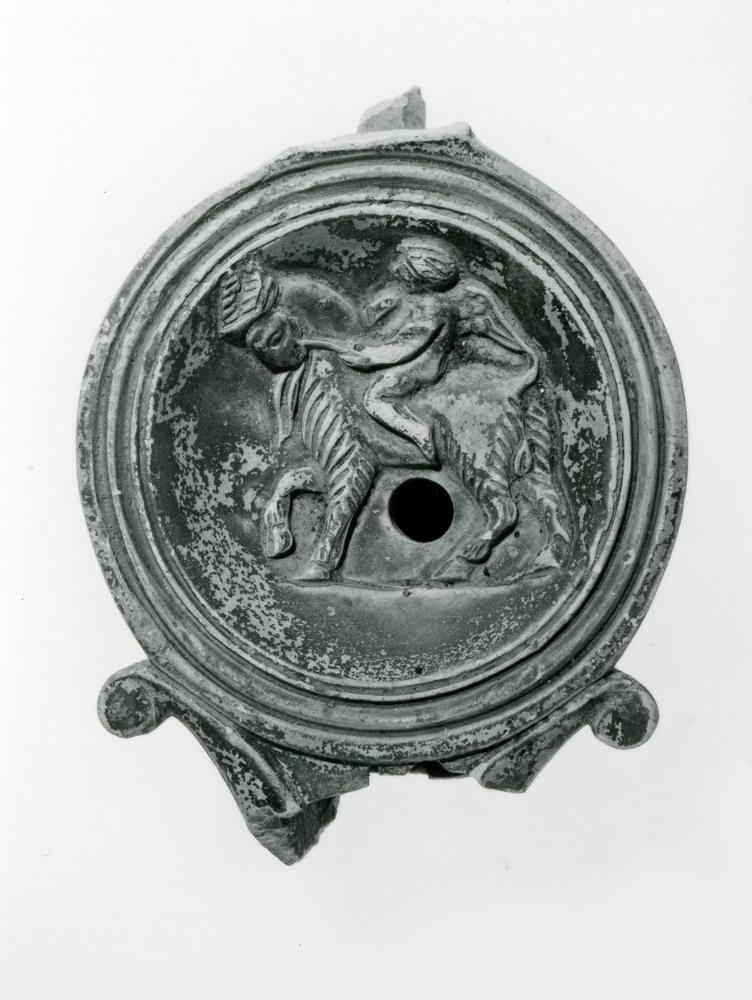 Mould-made pottery lamp decorated on the discus with a Cupid riding a goat. The nozzle has an air-slit, and is mainly missing. The handle is mainly missing. The lamp stands on a base-ring. Covered with a brown slip.