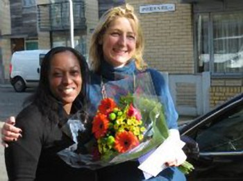 Melissa Nicholas (left) Family Co-ordinator at Home-Start Lambeth presenting flowers to Sophia Ruck for her work volunteering