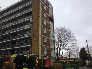 Firefighters stand outside the charred flat after bringing the blaze under control