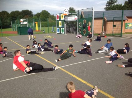 "Year 4 White ""Stretch out"" with Mr Burges in P.E. after working hard on an athletics circuit involving agility, balance and co-ordination."