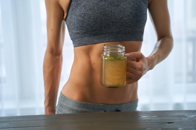 sporty-woman-drinking-a-hot-bone-broth-in-a-cup