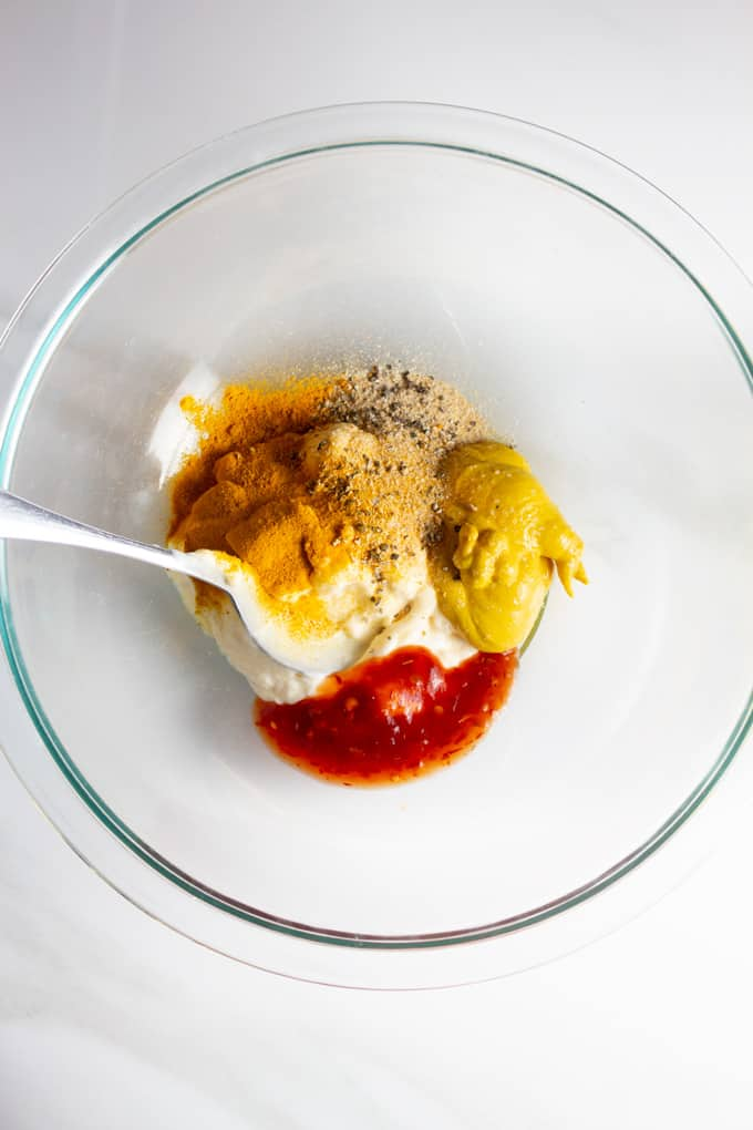 Mix of spices, mayonnaise, hot sauce and mustard in a glass bowl