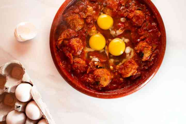 Raw eggs cracked on top of tagine to slowly poach them in the sauce.