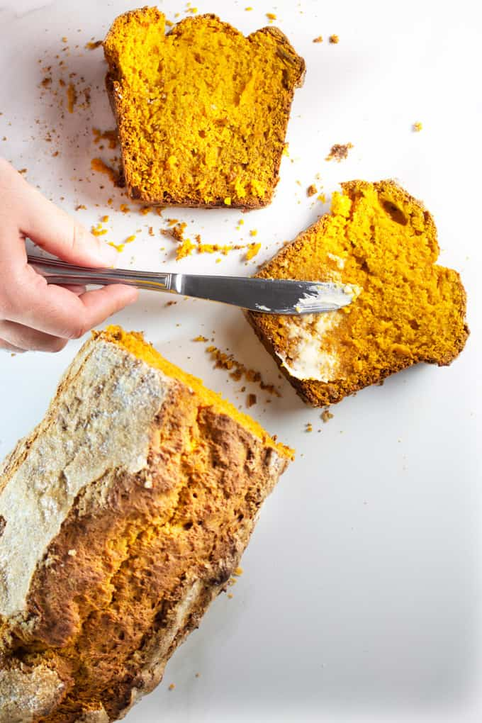 Sliced pumpkin bread being buttered