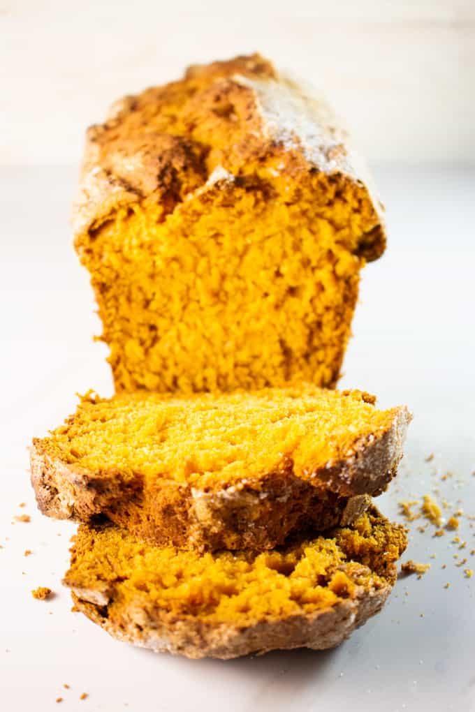 Sliced pumpkin bread on a white surface