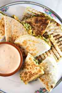 Vegan White Bean Quesadillas served on a large plate with dip on the side
