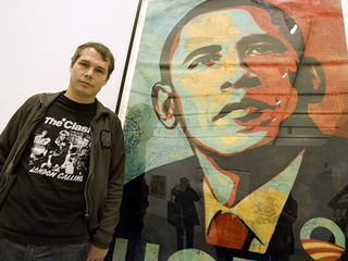 """Artist Shepard Fairey poses beside his """"Obama HOPE"""" image, part of an exhibit of his work at the Institute of Contemporary Art"""