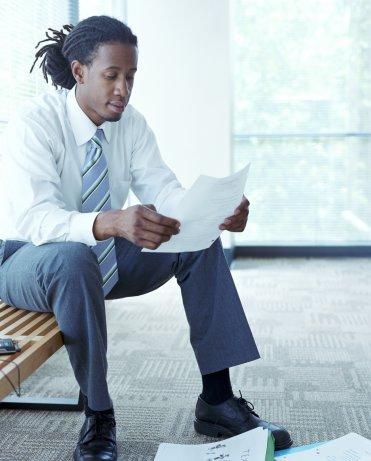 Businessman reading paper (blue tone)
