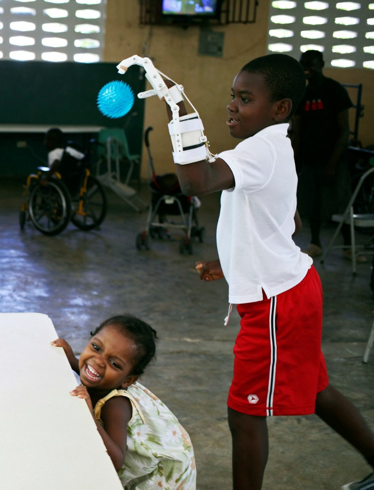 Handicapped Haitian boy Stevenson Joseph (R), practices using a 3D-printed prosthetic hand at the orphanage where he lives in Santo, near Port-au-Prince, April 28, 2014. REUTERS/Marie Arago